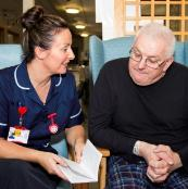 nurse reading leaflet with patient
